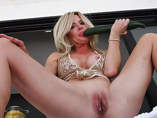 Mature sticks a big cucumber into her fine pussy