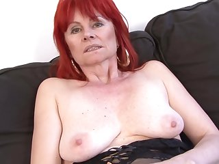Red haired granny in erotic undergarments is having random lovemaking with a black guy, on the sofa